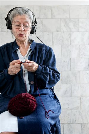 Woman Knitting and Listening to Headphones Stock Photo - Premium Royalty-Free, Code: 600-06144861