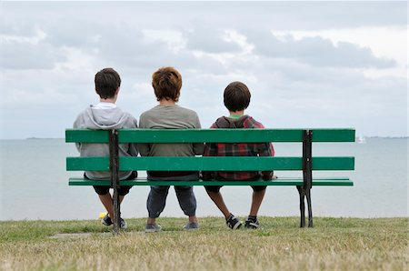 Back View of Mother and Sons Sitting on Park Bench, Ile de Re, France Stock Photo - Premium Royalty-Free, Code: 600-06334390