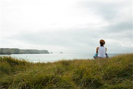 Woman Sitting and Looking into the Distance at the Beach, Camaret-sur-Mer, Crozon Peninsula, Finistere, Brittany, France Stock Photo - Premium Royalty-Free, Code: 600-06382811