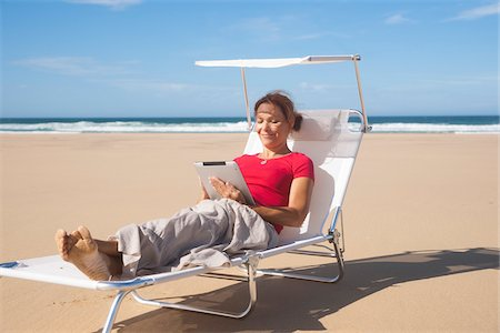 red chair - Woman Using Tablet at the Beach, Camaret-sur-Mer, Crozon Peninsula, Finistere, Brittany, France Stock Photo - Premium Royalty-Free, Code: 600-06382825