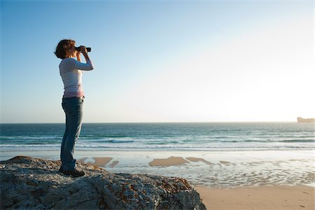 Woman Looking into the Distance Using Binoculars at the Beach, Camaret-sur-Mer, Crozon Peninsula, Finistere, Brittany, France Stock Photo - Premium Royalty-Free, Code: 600-06382829