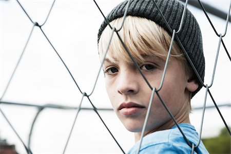 Portrait of Boy Looking Through Chain Link Fence, Mannheim, Baden-Wurttemberg, Germany Stock Photo - Premium Royalty-Free, Code: 600-06382847