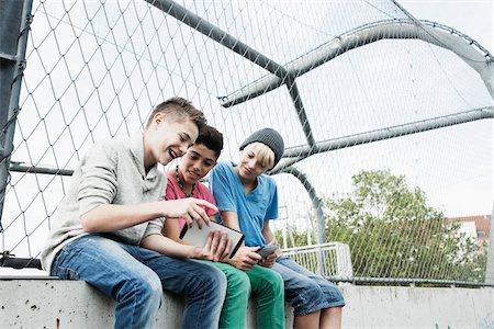 Three Boys Playing Video Games in Playground, Mannheim, Baden-Wurttemberg, Germany Stock Photo - Premium Royalty-Free, Code: 600-06382850