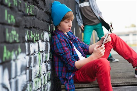 Boy Sitting and using a Tablet PC Outdoors, Mannheim, Baden-Wurttemberg, Germany Stock Photo - Premium Royalty-Free, Code: 600-06397438