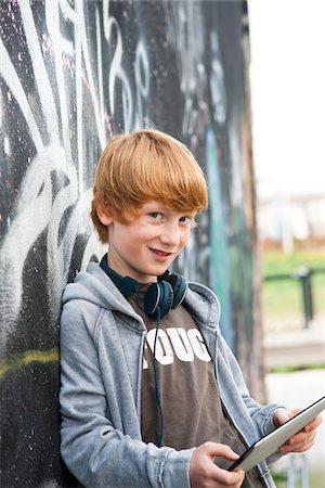 Boy wearing Headphones using Tablet PC, Mannheim, Baden-Wurttemberg, Germany Stock Photo - Premium Royalty-Free, Code: 600-06397439