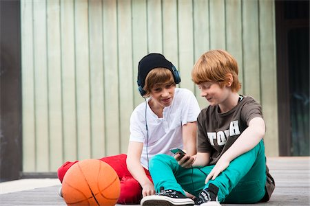 Boys using MP3 Player Outdoors, Mannheim, Baden-Wurttemberg, Germany Stock Photo - Premium Royalty-Free, Code: 600-06397449