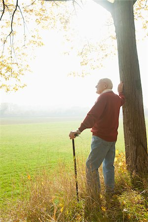 Senior Man with Cane Standing by Tree, Lampertheim, Hesse, Germany Stock Photo - Premium Royalty-Free, Code: 600-06397467