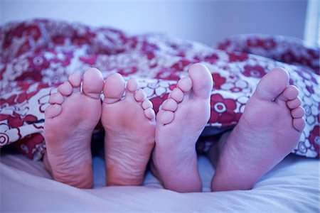 sole - Woman's Feet and Man's Feet Sticking Out of Blanket in Bed, Iceland Stock Photo - Premium Royalty-Free, Code: 600-06407816