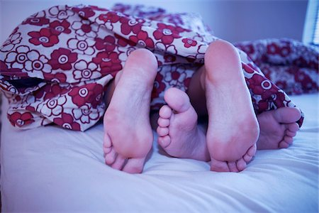 Woman's Feet and Man's Feet Sticking Out of Blanket in Bed, Iceland Stock Photo - Premium Royalty-Free, Code: 600-06407818