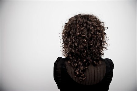 Woman with Curly Brown Hair from the Back in Studio Stock Photo - Premium Royalty-Free, Code: 600-06407883