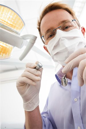 dentistry - Dentist wearing Surgical Mask and Holding Dental Instruments looking down, Germany Stock Photo - Premium Royalty-Free, Code: 600-06438918