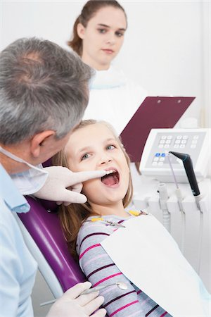preteen open mouth - Dentist touching Girl's tooth and Hygienist with Clipboard during Appointment, Germany Stock Photo - Premium Royalty-Free, Code: 600-06438929