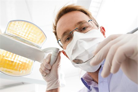 dentistry - Dentist wearing Surgical Mask Adjusting Light and looking down, Germany Stock Photo - Premium Royalty-Free, Code: 600-06438920