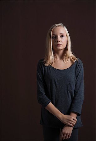 female only - Portrait of Blond, Teenage Girl Looking at Camera, Studio Shot on Black Background Stock Photo - Premium Royalty-Free, Code: 600-06438952