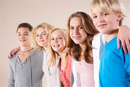 Portrait of Group of Teenage Boys and Girls, Standing in a Row with Arms around Shoulders, Studio Shot on White Background Stock Photo - Premium Royalty-Free, Code: 600-06438966