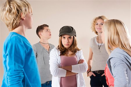 Portrait of Teenage Girl wearing Baseball Hat Looking at Camera, Standing in the Middle of Group of Teenage Boys and Girls, Studio Shot on White Background Stock Photo - Premium Royalty-Free, Code: 600-06438967