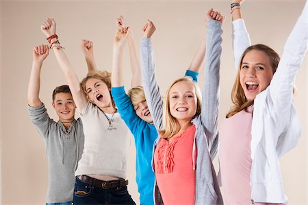 Portrait of Group of Teenage Boys and Girls with Arms in Air, Smiling and Looking at Camera, Studio Shot on White Background Stock Photo - Premium Royalty-Free, Code: 600-06438969