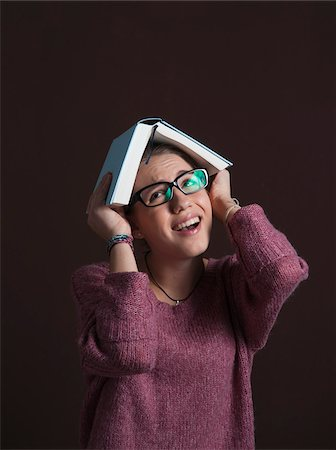 pressure - Portrait of Teenage Girl wearing Eyeglasses, holding Open Book over Head with Anxious Expression, Studio Shot on Black Background Stock Photo - Premium Royalty-Free, Code: 600-06438962