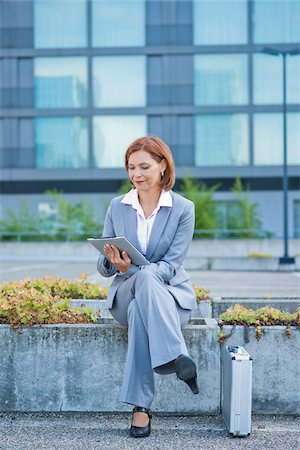 Businesswoman Sitting Outside in front of Office Building using Tablet PC, Niederrad, Frankfurt, Germany Stock Photo - Premium Royalty-Free, Code: 600-06438975