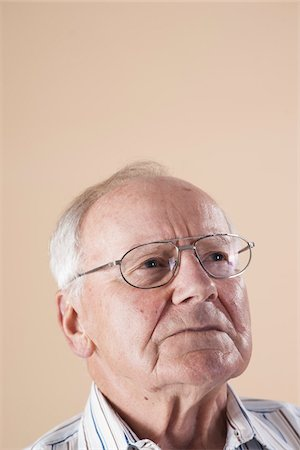 Portrait of Senior Man wearing Aviator Eyeglasses and Looking up into the Distance with Concerned Expression in Studio on Beige Background Stock Photo - Premium Royalty-Free, Code: 600-06438977