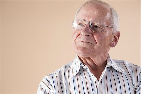 Portrait of Senior Man wearing Aviator Eyeglasses and Looking up into the Distance with Confident Expression in Studio on Beige Background Stock Photo - Premium Royalty-Free, Code: 600-06438978