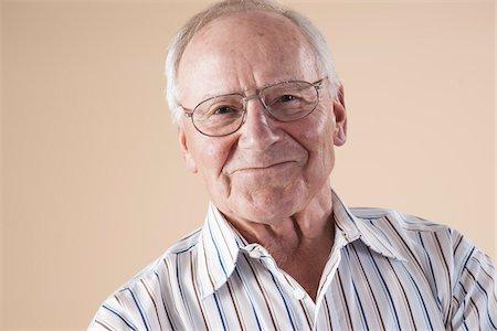 Portrait of Senior Man wearing Aviator Eyeglasses, Looking at Camera Smiling, in Studio on Beige Background Stock Photo - Premium Royalty-Free, Code: 600-06438979