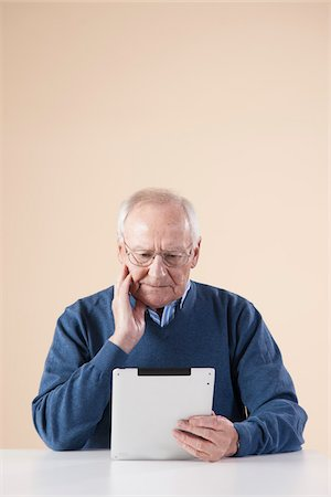 Senior Man Sitting at Table, Looking at Tablet PC, Studio Shot on Beige Background Stock Photo - Premium Royalty-Free, Code: 600-06438984
