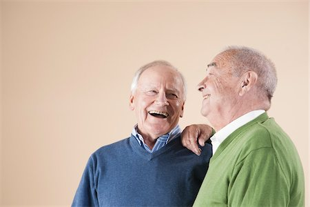 Portrait of Two Senior Men Laughing Together, Studio Shot on Beige Background Stock Photo - Premium Royalty-Free, Code: 600-06438985