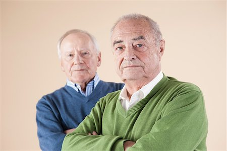Portrait of Two Senior Men Looking at Camera, Studio Shot on Beige Background Stock Photo - Premium Royalty-Free, Code: 600-06438987