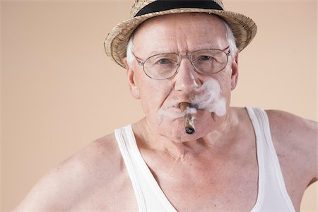 Portrait of Senior Man wearing Undershirt and Straw Hat while Smoking Cigar, Studio Shot on Beige Background Stock Photo - Premium Royalty-Free, Code: 600-06438988