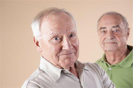 Portrait of Two Senior Men Looking at Camera, Studio Shot on Beige Background Stock Photo - Premium Royalty-Free, Code: 600-06438989