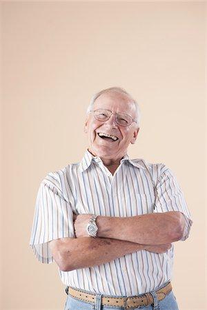 Portrait of Senior Man wearing Aviator Eyeglasses, Looking at Camera Laughing, in Studio on Beige Background Stock Photo - Premium Royalty-Free, Code: 600-06438980