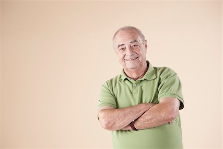 Portrait of Senior Man with Arms Crossed, Looking at Camera Smiling, Studio Shot on Beige Background Stock Photo - Premium Royalty-Free, Code: 600-06438990
