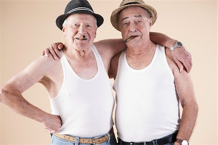 Portrait of Two Senior Man wearing Undershirts and Hats while Smoking Cigars with Arms around Shoulders, Studio Shot on Beige Background Stock Photo - Premium Royalty-Free, Code: 600-06438991