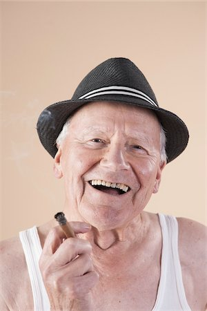 Close-up Portrait of Senior Man wearing Undershirt and Hat while Smoking a Cigar and Smiling, Studio Shot on Beige Background Stock Photo - Premium Royalty-Free, Code: 600-06438992