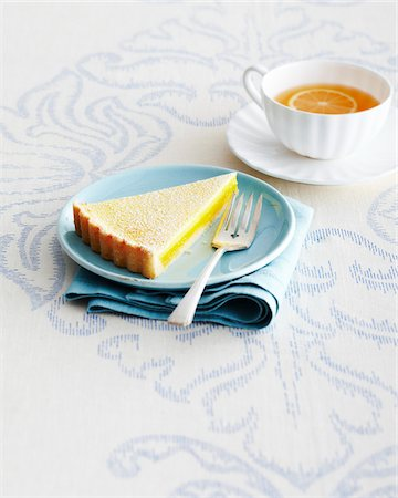 Slice of Lemon Tart and Fork on Blue Plate with Cup and Saucer of Herbal Tea on Tablecloth in Studio Stock Photo - Premium Royalty-Free, Code: 600-06431335