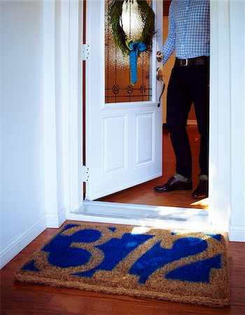 Man Opening Door to Home with Welcome Mat with House Number and Wreath on Door, Toronto, Ontario, Canada Stock Photo - Premium Royalty-Free, Code: 600-06431336