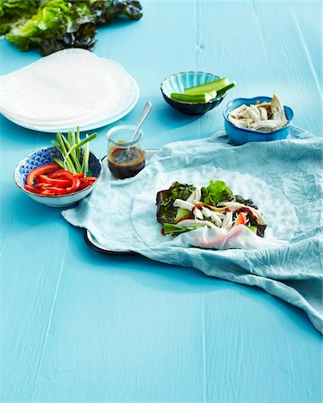 Rice Wrap on Blue Table Cloth with Bowls of Ingredients on Blue Wooden Table in Studio Stock Photo - Premium Royalty-Free, Code: 600-06431332