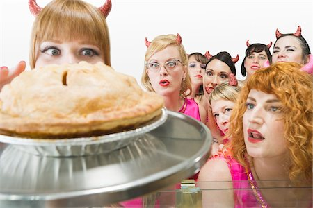 quirky - Women Wearing Devil Horns Looking at Apple Pie Stock Photo - Premium Royalty-Free, Code: 600-06431365