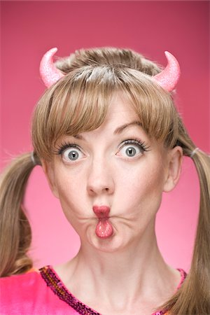 pucker - Portrait of Woman Wearing Devil Horns and Making Faces Stock Photo - Premium Royalty-Free, Code: 600-06431429