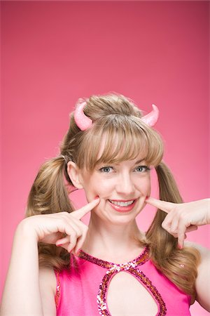 Portrait of Woman Wearing Devil Horns and Making Faces Stock Photo - Premium Royalty-Free, Code: 600-06431431