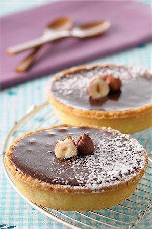 sweet   no people - Close-up of Chocolate Tarts on Cooling Rack Topped with Nuts and Icing Sugar Stock Photo - Premium Royalty-Free, Code: 600-06451971