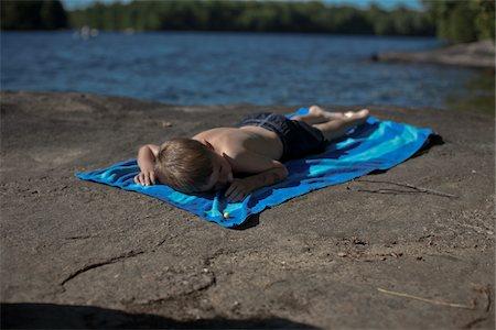 Boy Lying on Beach Towel on Rocks by Lake, Muskoka, Ontario, Canada Stock Photo - Premium Royalty-Free, Code: 600-06452051