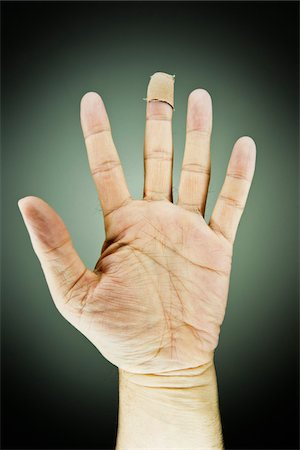 five - Close-up of Male Left Hand with Bandage on Middle Finger, Studio Shot Stock Photo - Premium Royalty-Free, Code: 600-06452108