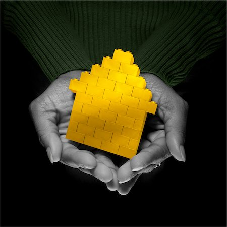 Close-up of Woman's Hands holding Yellow Brick House, Studio Shot Stock Photo - Premium Royalty-Free, Code: 600-06452123