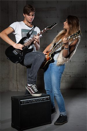 Young Man and Teenage Girl Playing Electric Guitars Stock Photo - Premium Royalty-Free, Code: 600-06465377