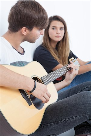 Young Man Playing Acoustic Guitar to Teenage Girl Stock Photo - Premium Royalty-Free, Code: 600-06465373