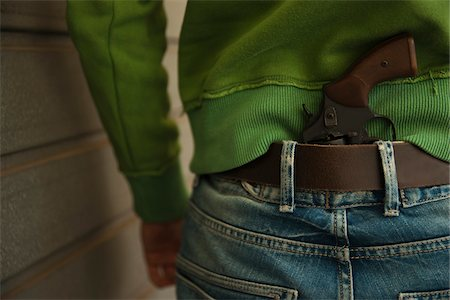 Close-up of Back of Young Man with Handgun Tucked into Waistband of Blue Jeans, Mannheim, Baden-Wurttemberg, Germany Stock Photo - Premium Royalty-Free, Code: 600-06486015