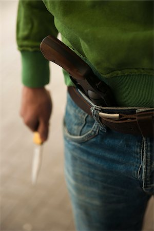 Close-up of Young Man holding Knife with Handgun tucked into Waistband of Blue Jeans, Mannheim. Baden-Wurttemberg, Germany Stock Photo - Premium Royalty-Free, Code: 600-06486018