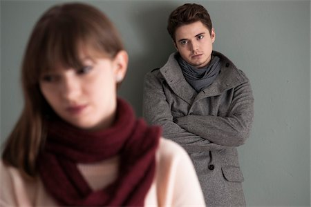 sad lovers break up - Portrait of Young Man Standing behind Young Woman, Looking at her Intensely, Studio Shot on Grey Background Stock Photo - Premium Royalty-Free, Code: 600-06486263